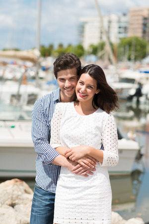 citytrip: Beautiful loving couple at a marine harbour standing in a close embrace smiling at the camera on a hot sunny summer day Stock Photo