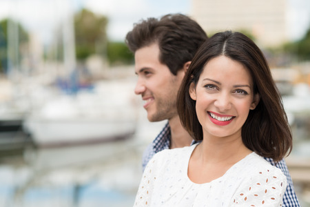 citytrip: Beautiful smiling woman with shoulder length long brunette hair posing with her husband at a small boat harbour at the coast with copyspace