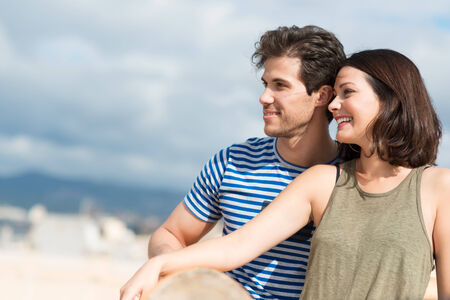 citytrip: Profile view of an attractive young couple sitting close together on a sandy beach looking out towards the ocean, with copyspace Stock Photo