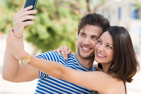 Vivacious attractive young couple taking a selfie on their mobile posing with their heads close together smiling happily at the camera photo