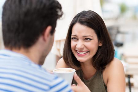 mujeres latinas: Feliz pareja tener un gran tiempo hablando sobre una taza de caf� Foto de archivo