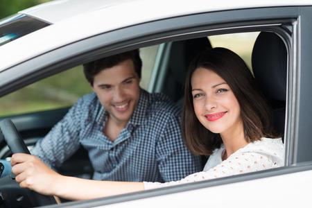 Mooie vrouw die haar man voor een rit op zoek door het open zijraam van de auto met een stralende glimlach van genot