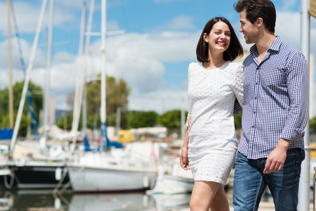strolling: Stylish attractive young couple strolling past a small boat harbour laughing as they chat and look into each others eyes