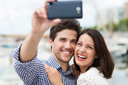 adult dating: Young couple taking a self portrait laughing as they pose close together for the camera on their smartphone outdoors in summer sunshine