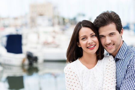 citytrip: Happy affectionate couple on summer vacation posing at a small boat harbour or marina standing close together and smiling at the camera, with copyspace Stock Photo