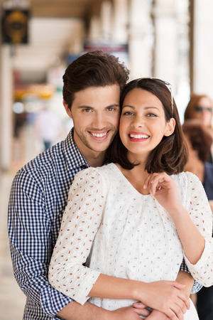 Loving beautiful young couple standing in a close intimate embrace smiling happily at the camera in an urban street photo