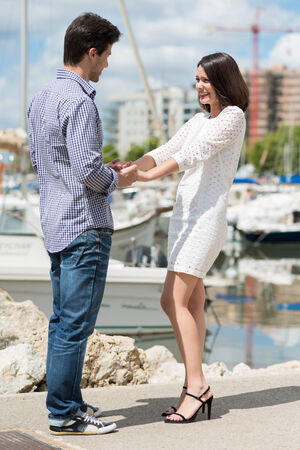 citytrip: Romantic young couple at a small boat marina standing facing each other holding hands and laughing happily in the warm sunshine Stock Photo