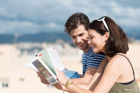 citytrip: Happy young couple paging through tourist brochures as they stand close together on a hot tropical beach in the summer sunshine smiling as they look up information