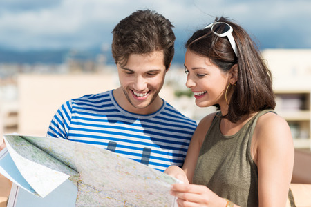 citytrip: Smiling young couple consult a tourist map as they stand together on a tropical beach enjoying a summer vacation Stock Photo