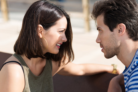 Profile view of an attractive young couple sitting staring intently into each other eyes Stock Photo