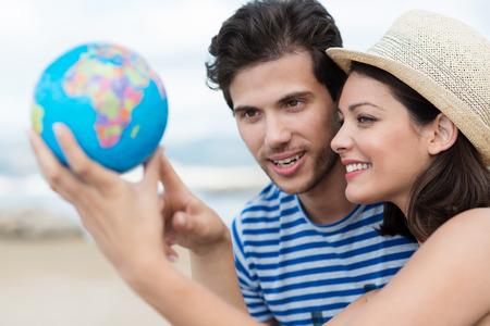 旅遊: 激動的年輕夫婦計劃他們的節日拿著一個地球儀,指著一個旅遊目的地,重點向有吸引力的女人在時尚草帽 版權商用圖片