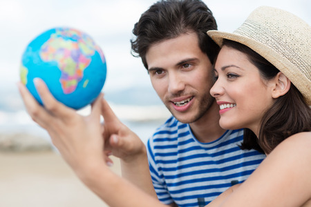 student travel: Excited young couple planning their holiday holding up a globe and pointing to a travel destination with focus to the attractive woman in a trendy straw hat