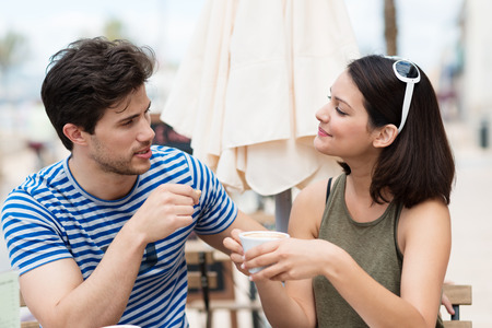 conversation: Romantic young couple drinking coffee outdoors seated at a table at a restaurant enjoying a relaxing conversation looking into each others eyes