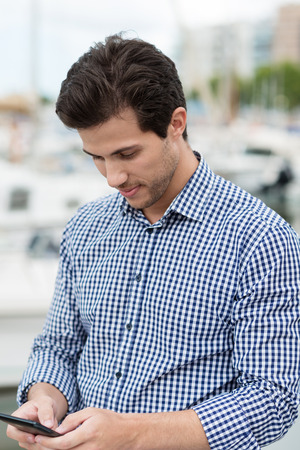 Portrait of a handsome unshaven young man wearing a casual blue checkered shirt while writing messages or browsing on his smart thin mobile phone, outdoors, with blurred yachts behind him photo