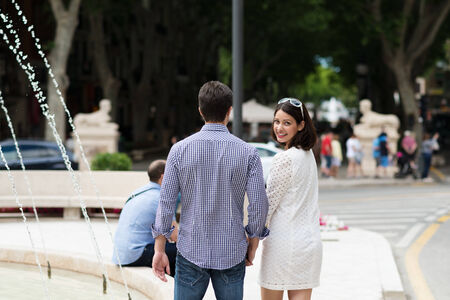 looking back: Young couple walking past an urban fountain with the attractive dark haired woman turning to smile over her shoulder at the camera