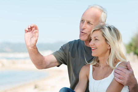 Loving mature couple enjoying a day at the sea standing in a close embrace overlooking the ocean having an animated discussion and gesturing photo