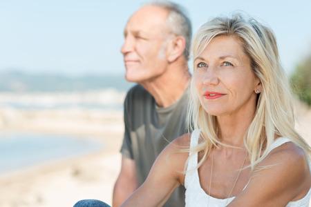 planificacion: Mujer de mediana edad pensativo relajante en el mar, sentado junto a su marido mirando hacia el cielo con una expresión contemplativa