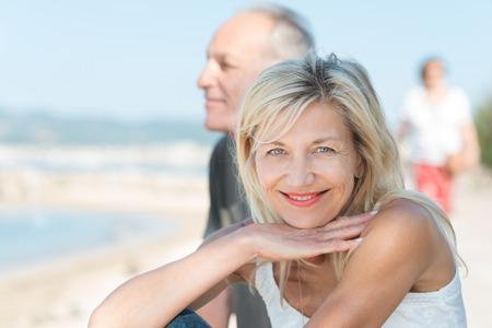 彼女の夫は、彼らは健康的なアクティブなライフ スタイルをお楽しみください、カメラに笑顔を浮かべてビーチで日焼け熟女