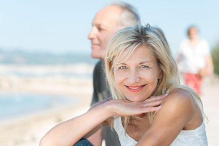 Smiling tanned mature woman at the beach with her husband turning to smile at the camera as they enjoy a healthy active lifestyle photo