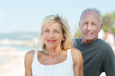 Attractive middle-aged couple on summer vacation at the seaside posing together on the beach smiling at the camera photo