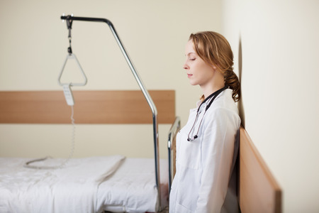 doctor burnout: Young female doctor standing with closed eyes leaning against the wall in a ward alongside an empty hospital bed as she takes a moment to gather herself together