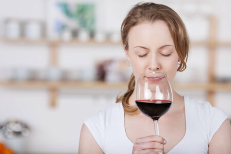 concentrates: Young woman savoring the bouquet of a glass of wine as she sniffs at the glass with her eyes closed in bliss as she concentrates on the smell, with copyspace indoors in the kitchen