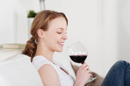 appreciating: Beautiful woman appreciating a glass of red wine smiling with satisfaction as she looks down at the glass tilted in her hands while enjoying a quiet evening at home Stock Photo