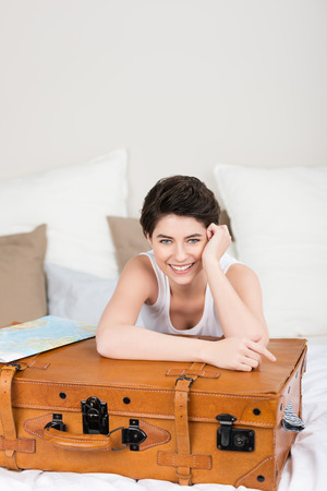 anticipating: Excited woman anticipating her annual vacation lying on her bed with her arms resting on her vintage leather suitcase smiling happily at the camera