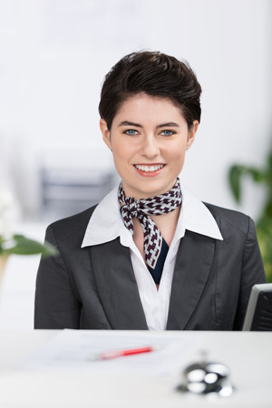 Beautiful elegant hotel receptionist with a lovely friendly smile in a stylish outfit with a scarf and a short modern haircut photo