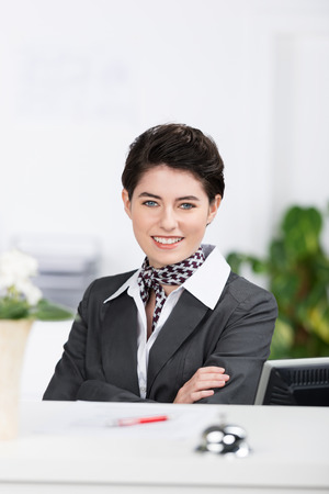 Beautiful confident stylish receptionist in a classical grey uniform with a neck scarf standing behind a hotel counter smiling at the camera with folded arms photo