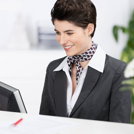 Beautiful elegant hotel receptionist or secretary wearing a stylish neck scarf sitting working at her computer with a smile photo