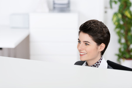 Caucasian beautiful modern young short-haired woman smiling while sitting behind the reception desk of a company or a welcoming hotel, with a blurred decorative plant in the background photo