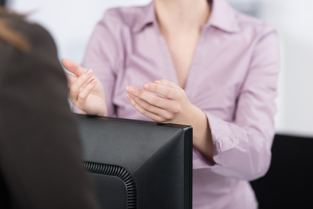 Hands of a businesswoman in a meeting gesticulating as she explains a point to a colleague