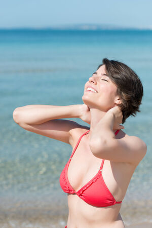 tilted: Beautiful woman basking in the sunshine standing with her head tilted back and eyes closed in bliss as she celebrates the freedom of her summer vacation