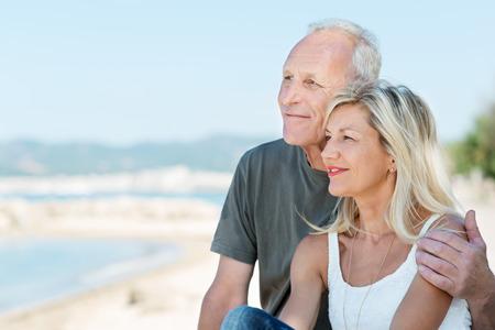 Liefdevolle senior paar op het strand zitten arm in arm lacht als ze uitkijken over de oceaan genieten van de zomerzon Stockfoto
