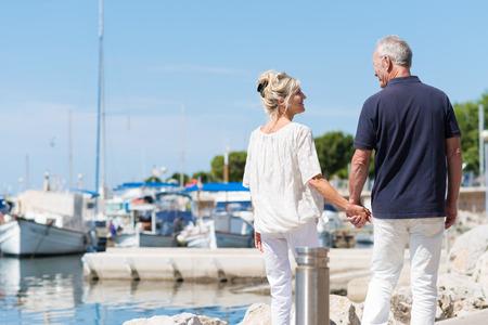 Älteres Paar genießen einen Tag an der Küste zu Fuß entfernt von der Kamera Hand in Hand an einem kleinen Bootshafen