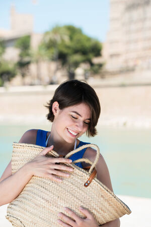 Smiling beautiful young female tourist hugging a big straw bag full of holiday mementos as she enjoys a sunny summer vacation in the tropics photo