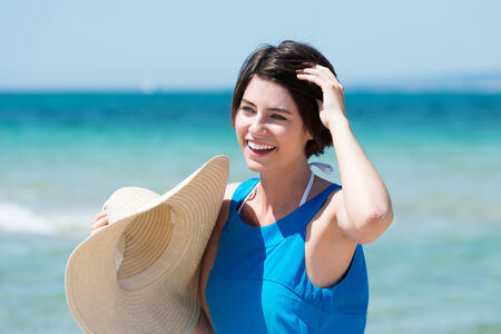 Beautiful laughing woman at the seaside standing in front of the ocean holding a wide brimmed straw sunhat with her hand to her short brunette hair photo