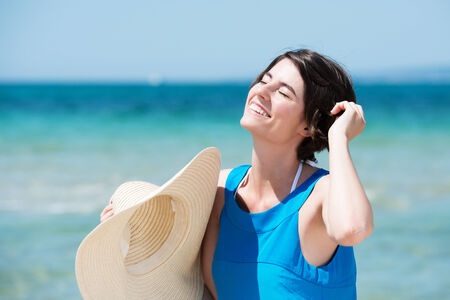 Beautiful woman basking in the sun standing on a tropical beach in front of a calm blue ocean with her head tilted to the sun and a lovely happy smile on her face as she holds her straw sunhat photo