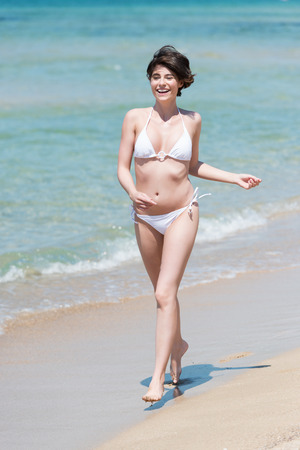 beautiful young woman in a white bikini walking along a sunny tropical beach laughing with enjoyment on her summer vacation photo