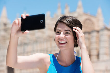 Happy beautiful young female tourist taking a selfie in Majorca posing in front of the cathedral holding up her mobile phone and laughing photo