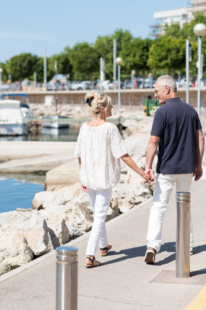 Middle aged couple strolling hand in hand past a small boat harbour on a hot summer day with their backs to the camera photo