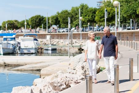 Gelukkig echtpaar van middelbare leeftijd lopen hand in hand langs een kleine boot jachthaven aan de kust als ze genieten van een actieve dag in de zomerzon