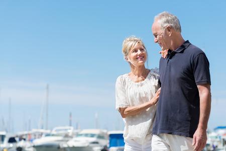 parejas de amor: Cari�oso atractiva pareja madura en el mar de pie sonriendo a los ojos delante de un puerto marino