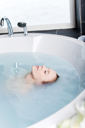 soaking: Beautiful woman in a spa bath floating in the blue water with her eyes closed in bliss and a serene peaceful expression