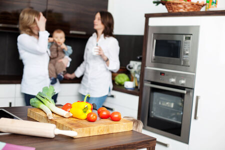 Vegetables on cutting board with women and babyboy in background at kitchen photo