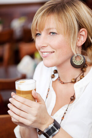cradling: Close up head and shoulders portrait of an attractive young blond woman with a gentle smile cradling a glass of beer in her hands Stock Photo