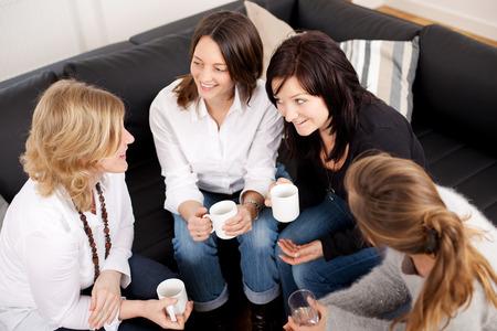 socializando: Vista de ángulo alto de amigas felices celebración de tazas de café mientras se está sentado en el sofá en casa Foto de archivo