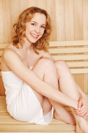 bathhouse: Beautiful natural woman in a sauna relaxing on the wooden bench wrapped in a fresh white towel smiling happily at the camera Stock Photo