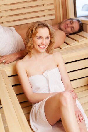 taking a wife: Attractive young couple taking a sauna together with the husband lying relaxing on the bench while his beautiful wife sits below smiling at the camera Stock Photo